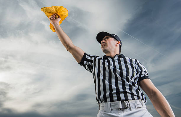 Below view of referee showing penalty against the sky. Low angle view of football judge holding a yellow flag against the sky. referee stock pictures, royalty-free photos & images