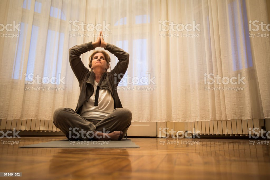 Below view of relaxed senior woman exercising Yoga at home. royalty-free stock photo