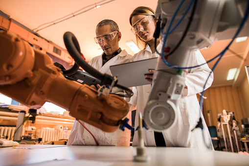 Low angle view of two engineers working on robotic arm in laboratory. Woman is using digital tablet.
