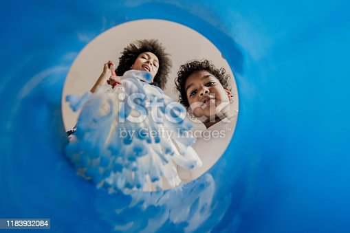 Low angle view of African American mother and her daughter dipping the mop into the bucket. Focus is on girl looking at camera. Copy space.