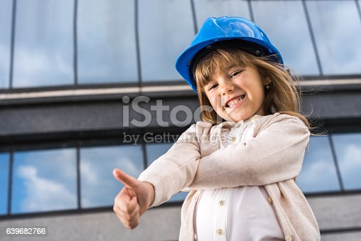 643843490istockphoto Below view of small architect showing thumbs up. 639682766