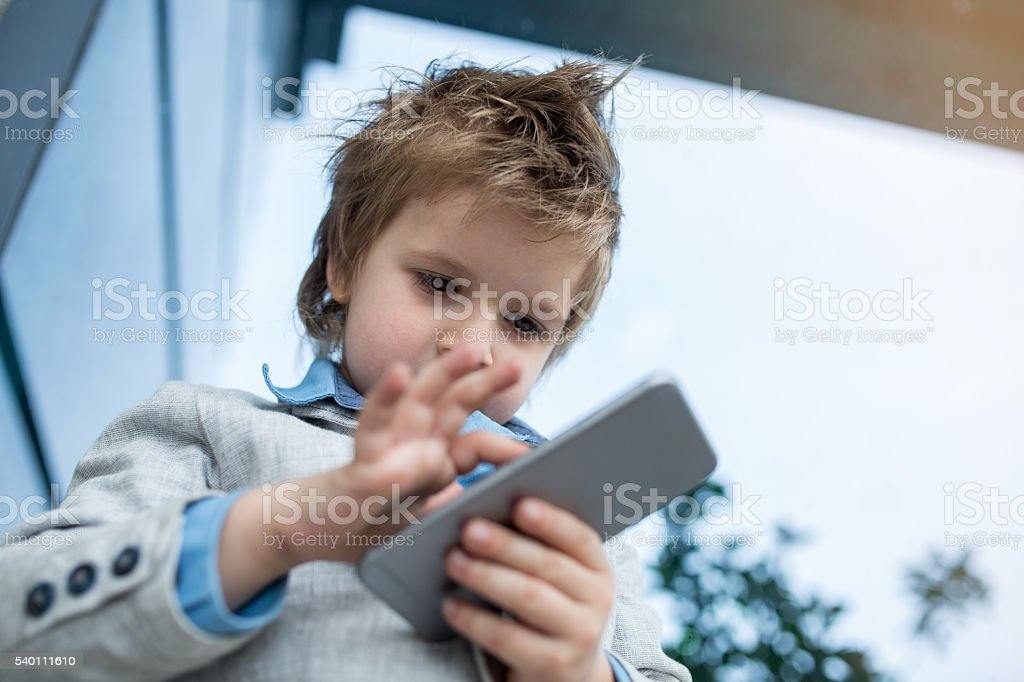 Below view of small boy using cell phone outdoors. stock photo