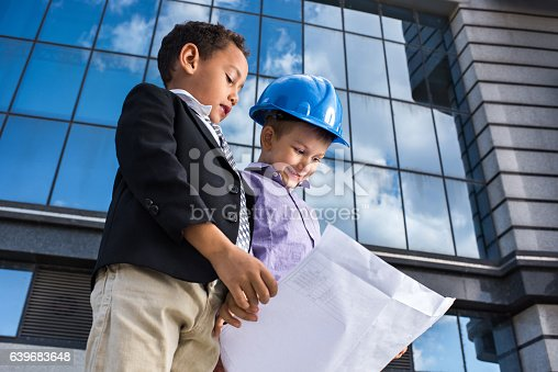 643843490istockphoto Below view of small business boys analyzing blueprints outdoors. 639683648