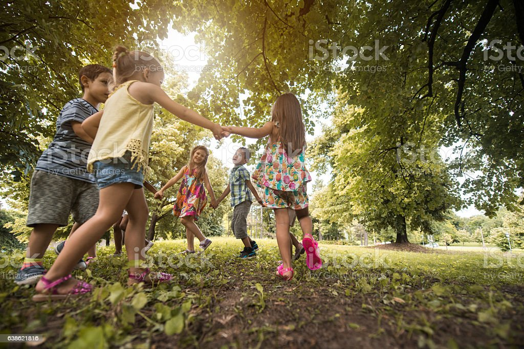 Below view of small friends playing ring-around-the-rosy in the park. - Photo