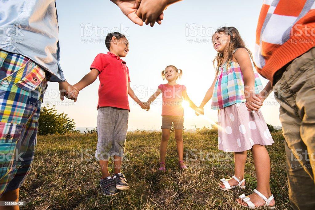 Au-dessous de vue de petite heureux amis se tenant les mains au coucher de soleil. - Photo