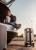 Low angle view of cute little boy sitting in a car trunk before his trip and looking away.