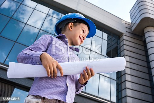 643843490 istock photo Below view of smiling little architect with blueprints outdoors. 643843546