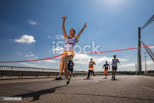 Low angle view of satisfied marathon runner celebrating her victory while crossing the finish line.