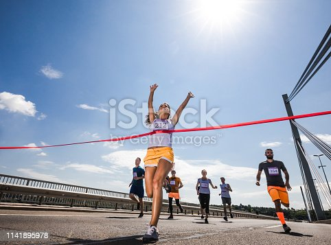Low angle view of female marathon runner celebrating victory while crossing the finish line with raised arms. Copy space.