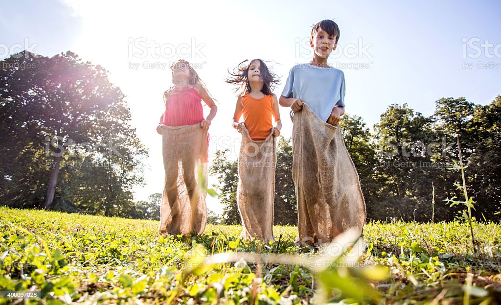 Below view of three happy kids on sack race outdoors. stock photo