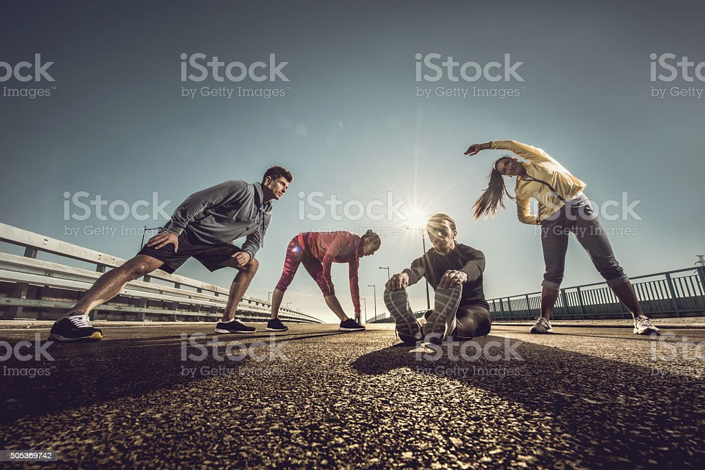 Below view of young athletes doing stretching exercises on road. stock photo