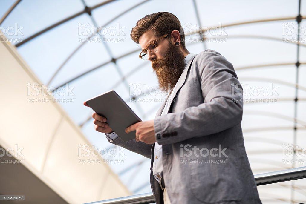 Below view of young businessman using digital tablet. zbiór zdjęć royalty-free