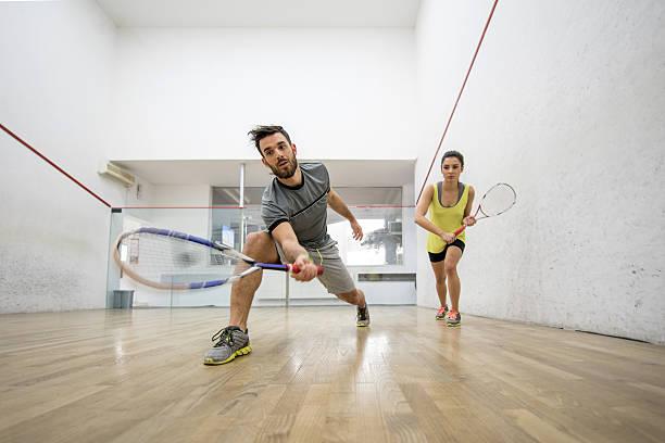 Unten Blick auf jungen Mann und Frau spielt Squash. – Foto