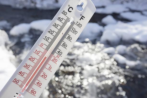 Below Zero degree Celsius temperature with frozen creek in background stock photo