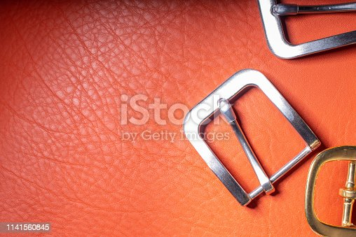 istock Belt buckles and coral leather background with empty space for mockup, template and text 1141560845