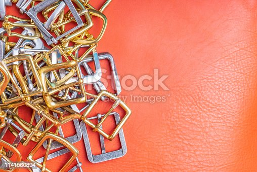 istock Belt buckles and coral leather background with empty space for mockup, template and text 1141560894