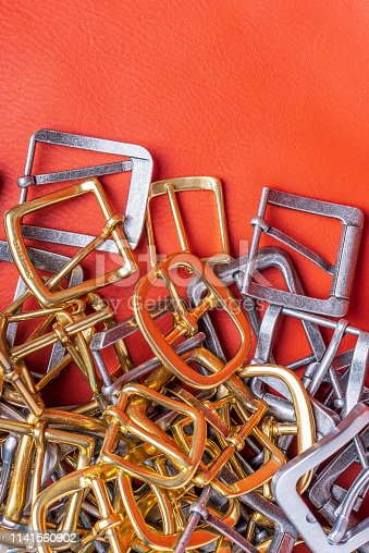 istock Belt buckles and coral leather background with empty space for mockup, template and text 1141560902
