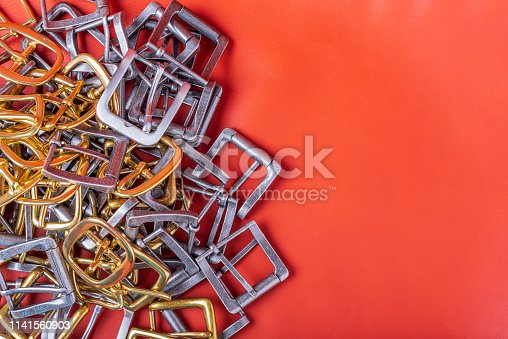 istock Belt buckles and coral leather background with empty space for mockup, template and text 1141560903