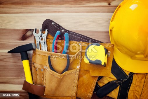 istock Belt with tools and yellow helmet on wood 484327585