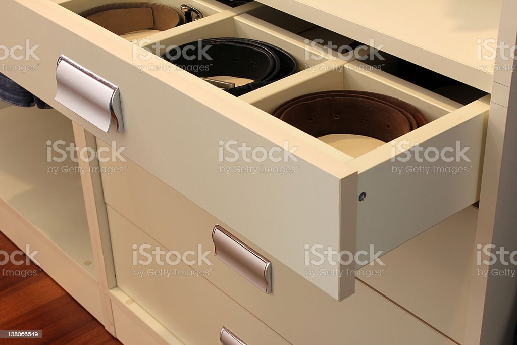 Belts coiled into white drawers stock photo