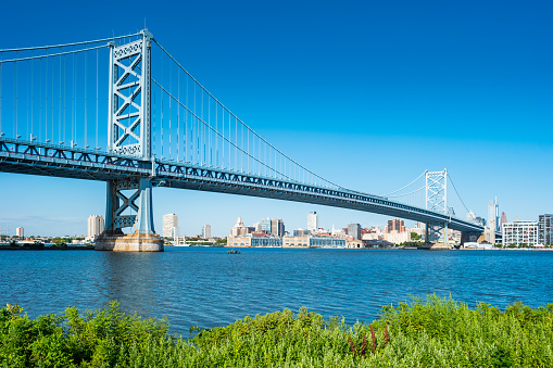 Ben Franklin Bridge and the Delaware River in downtown Philadelphia USA on a sunny blue sky day.