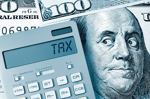 Tax. Benjamin Franklin looking calculator on One Hundred Dollar Bill.