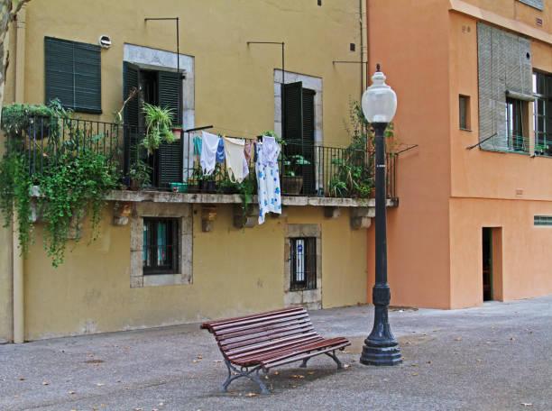 eine bank und street laterne auf dem hintergrund der bunten fassade des gebäudes und einen balkon mit pflanzen in girona - orangenscheiben trocknen stock-fotos und bilder