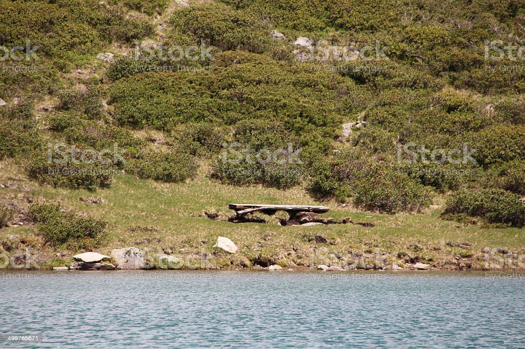 Bench at a Mountain Lake in Spring Season stock photo