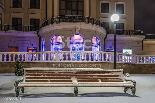 Uglich, Russia - December 26, 2020. A bench covered with snow in the park against the backdrop of the building's facade, decorated with Christmas festive illumination. The bench in the photo is located in a public park on the Volga River embankment behind the fence of the hotel's summer cafe.