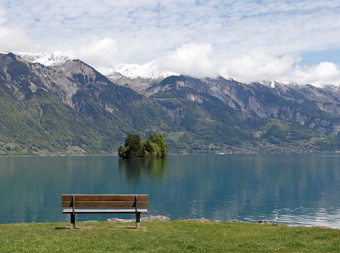 Bench facing towards picturesque lake and mountain scenery. Showing a tranquil and relaxing scene for recharging energy.