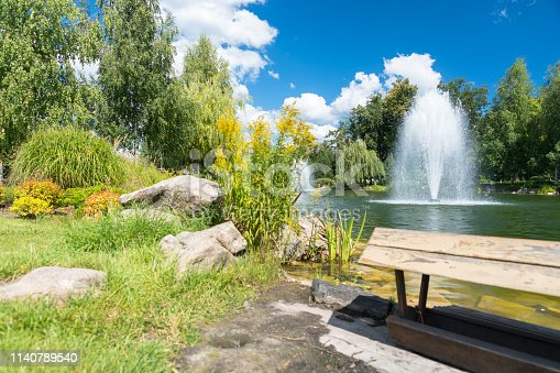 Bench in a park overlooking ornamental fountains in a lake surrounded by leafy green trees in a scenic landscape