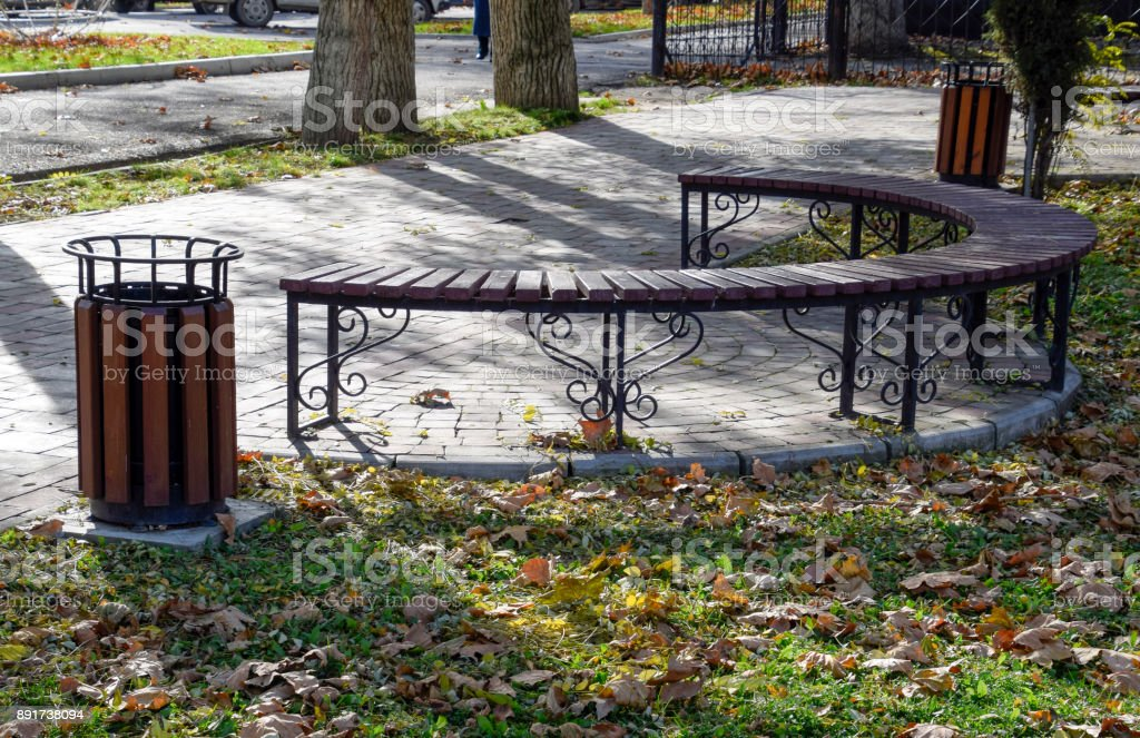 Bench In An Autumn Park Pavement Of Tiles And Garbage Can