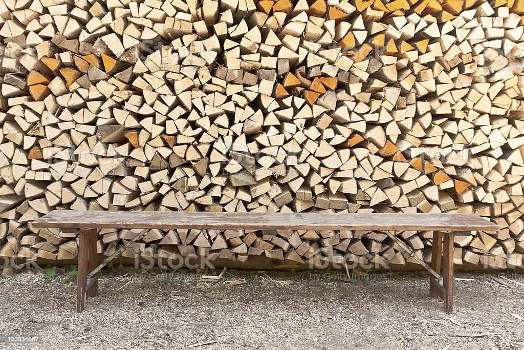 Bench In Front Of Wood Pile royalty-free stock photo