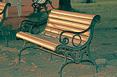 Close up of a bench made of mild steel & wooden strips in a garden