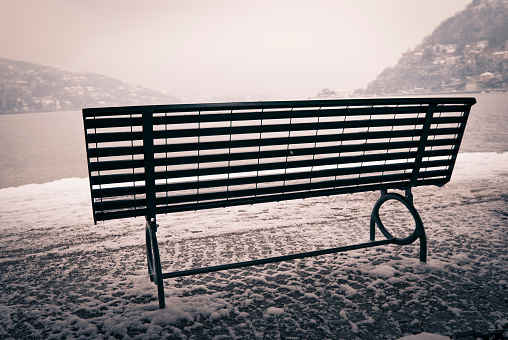 Bench in the snow against Lake Como.