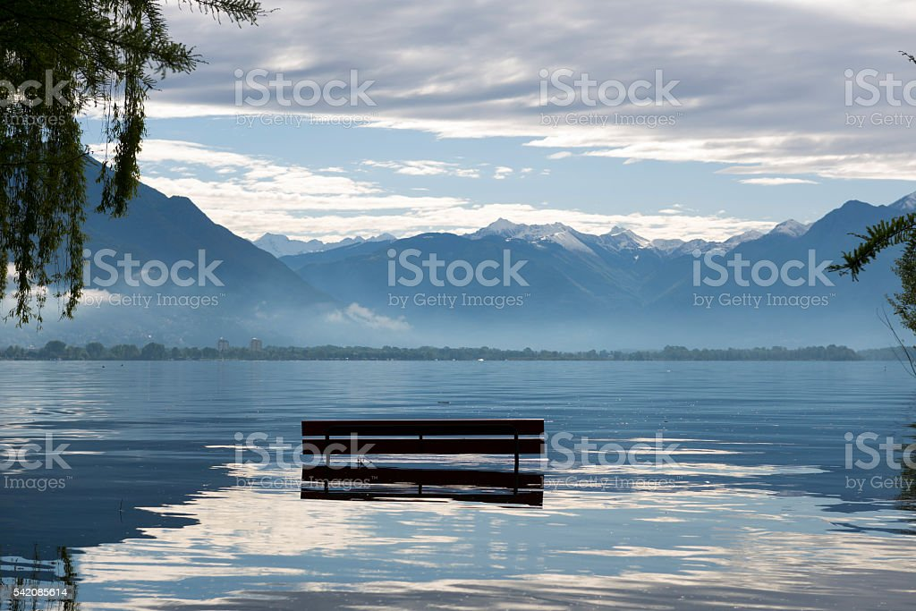 Bench on a flooding alpine lake stock photo