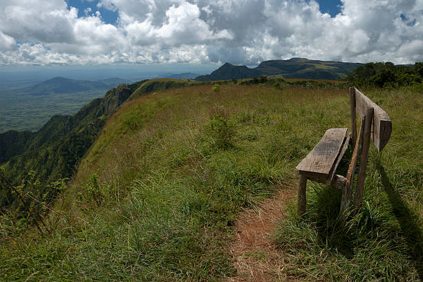 скамья на краю горы, сторону с видом на plains ниже. - плато стоковые фото и изображения