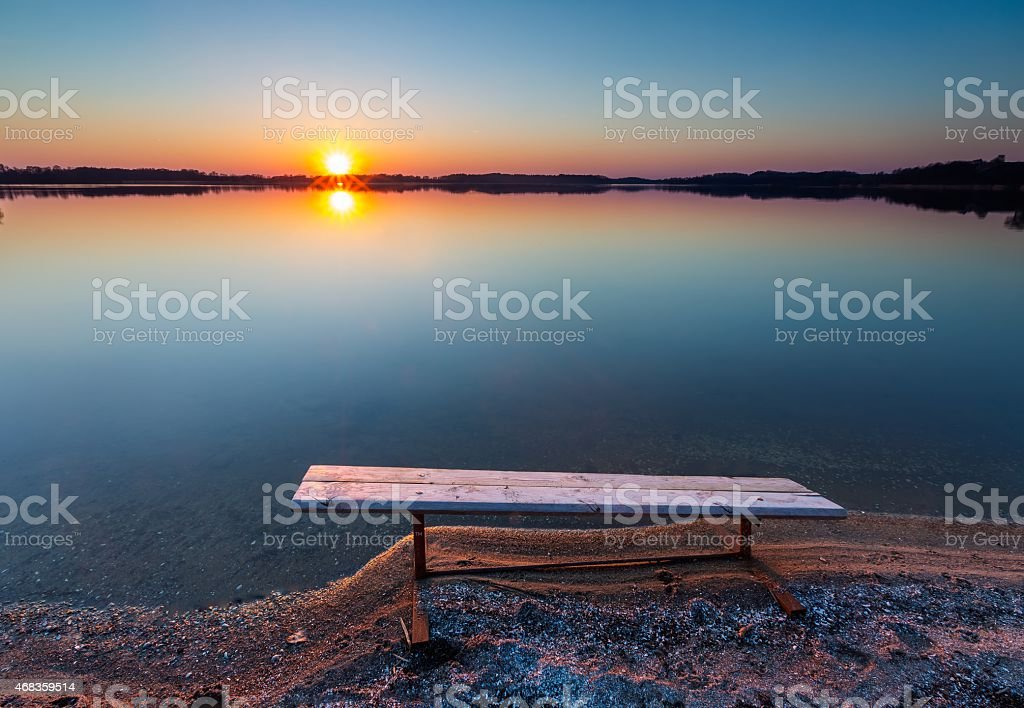 Bench on lake shore at sunset royalty-free stock photo