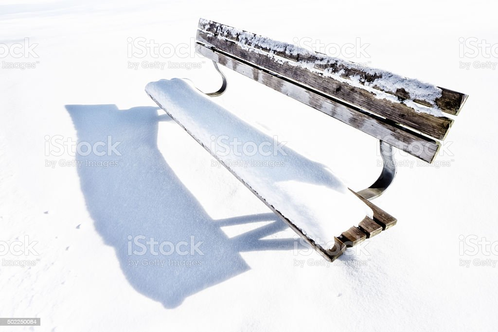 bench on snowy winter day stock photo