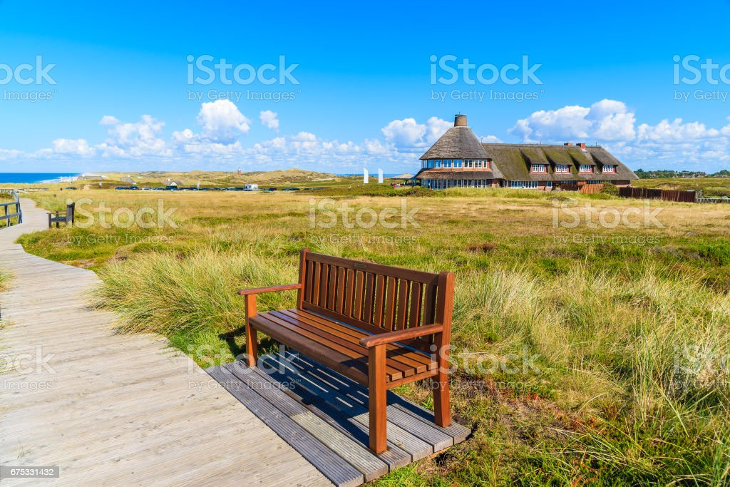 Bench on walking path along a coast of Sylt island and typical Frisian guest house in background, Germany stock photo