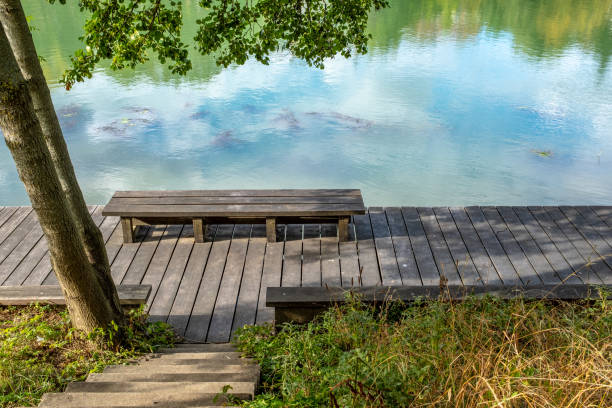 Bench overlooking the Marne River, France Bench overlooking the Marne River upon which a blue sky with clouds are reflecting. Taken late afternoon in Nogent-sur-Marne, France marne stock pictures, royalty-free photos & images