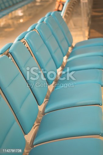 istock Bench seats for traveller or tourist on corridor in waiting area of airport departure flight or bus terminal building interior 1142791728