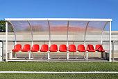 スタジアムで選手の赤いプラスチック シートとベンチ