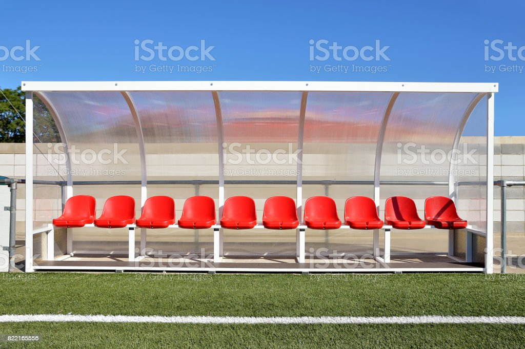 bench with red plastic seats for players at the stadium stock photo