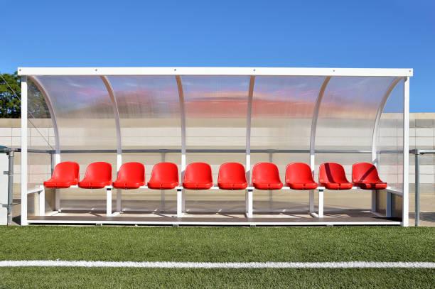 bänk med röd plast platser för spelare på stadion - bench bildbanksfoton och bilder