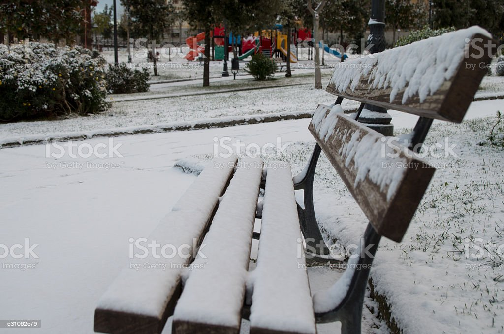 Bench with snow in Torre Del Greco park stock photo