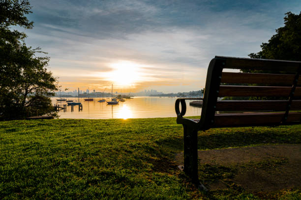 Bench_overlooking_boats_on_water_morning_clouds stock photo