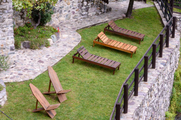 Benches and wooden deckchairs on a green mountain meadow. stock photo