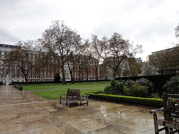 Benches in Grosvenor Square After the Rain Wooden benches can be seen in Grosvenor Square in London after the rain has fallen. In the background we can see the fancy housing developments and the statue of Roosevelt can be seen in the distant. The trees stand guard as they slowly gain back their leaves. The green grass shines brighter after the earlier shower.  mayfair stock pictures, royalty-free photos & images