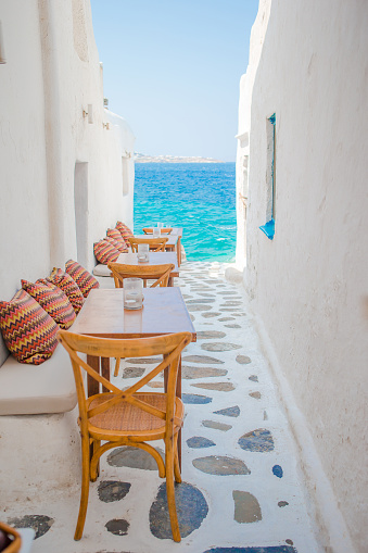 istock Benches with pillows in a typical greek outdoor cafe in Mykonos with amazing sea view on Cyclades islands 910619344